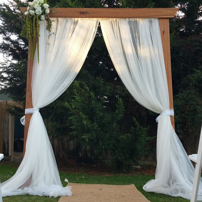 timber wedding arbour with curtains