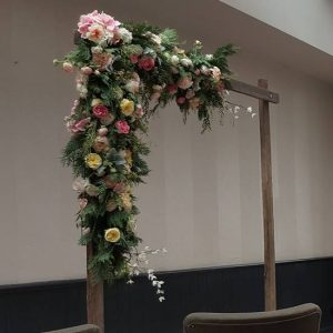 wooden wedding arbour with pink flowers