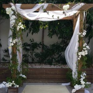 wooden Wedding arch with white drapping and flowers