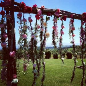 wedding flowers hanging from wedding arch